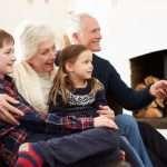 Grandparents Sitting On Sofa Watching TV With Grandchildren
